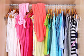 Female clothes on hangers in wardrobe — Stock Photo