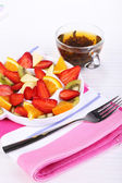 Various sliced fruits on plate on table close-up — Stock fotografie