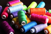Multicolor sewing threads on wooden background — Stock Photo
