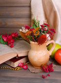 Beautiful bouquet of bright flowers in pitcher on table on grey background — Stock Photo