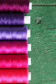 Multicolor sewing threads on wooden background — Foto de Stock