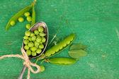 Fresh green peas in spoon on wooden table — Stockfoto