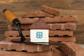 Wooden toy house on trowel and tiles, close up  — Stock Photo