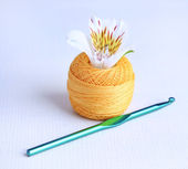 Colorful clew, crochet hook and fresh flower on light background — Stock Photo
