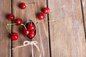 Ripe sweet cherries in spoon on wooden table — Stock Photo