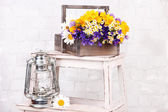 Beautiful flowers in crate with kerosene lamp on ladder on light background — Stock Photo