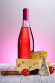 Pink wine and different kinds of cheese on colorful background — Stock Photo