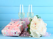 Beautiful wedding bouquet, gift box and wine glasses on  color background — Stock Photo