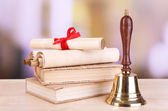 Gold retro school bell with books on table on bright background — Stock Photo