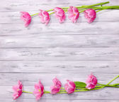 Beautiful flowers on color wooden background — Stock Photo
