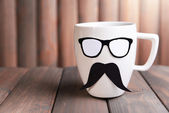 Cup with mustache on table on wooden background — Stockfoto