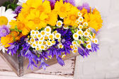 Beautiful flowers in crate on light background — Stock Photo