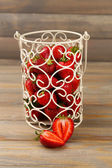 Red ripe strawberries in decorative vase on wooden background — Stock Photo