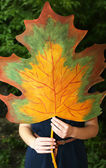 Girl holding decorative maple leaf on dark background — Stock Photo