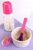 Baby bottle with milk and dirty bowl on napkin close up — Stock Photo