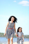 Happy mom and daughter. Walk on the beach — Stock Photo