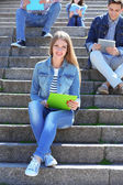 Happy students sitting on stairs in park — Photo