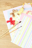 Paper for scrapbooking and tools, on wooden table — Stock Photo