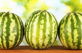 Ripe watermelons on green background close-up — Stock Photo