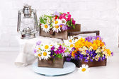 Beautiful flowers in crates with kerosene lamp on wooden stand on light background — Stock Photo