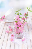 Beautiful fruit blossom in glass on table on light background — Stock Photo