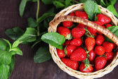 Ripe sweet strawberries in wicker basket and mint leaves on wooden background — Stockfoto
