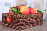 Ripe sweet apples with leaves in wicker crate on light background — Stockfoto