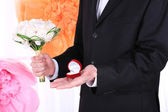 Man holding wedding bouquet and ring on decorative background — Stock fotografie