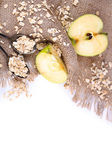 Apple with oatmeal and vintage spoons on sackcloth, isolated on white  — Stock Photo