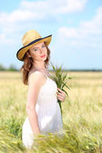 Beautiful young woman with ears in field — Stock Photo