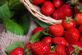Ripe sweet strawberries in wicker basket and mint leaves on wooden background — Stock Photo