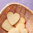 Lavender cookies in wicker basket, on color wooden background — Stock Photo #47989693