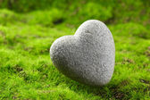 Grey stone in shape of heart, on grass background — Stock Photo