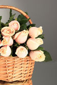 Beautiful bouquet of roses in basket on grey background — Stock fotografie
