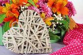 Tablo üzerinde dekoratif kalp ile sandık çiçek kompozisyon yakın çekim — Stok fotoğraf