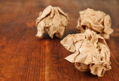 Crumpled paper balls on wooden background — Stock Photo