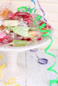 Tasty candies on plate on table on wooden background — Stok fotoğraf