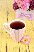 Fragrant tea with flowers on wooden table close-up — Stock Photo
