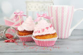 Tasty cup cakes with cream on grey wooden table — Stock Photo