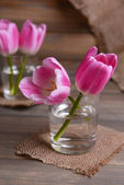 Beautiful tulips in bucket in vase on table on grey background — Stock Photo