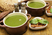 Tasty soup in saucepans on wooden table, close up — Stock Photo