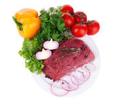 Raw beef meat with vegetables on plate isolated on white — Zdjęcie stockowe