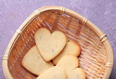 Lavender cookies in wicker basket, on color wooden background — Zdjęcie stockowe