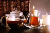 Composition with tea in glass teapot and candles on table, on dark background — Stock Photo
