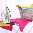 Basket with laundry and ironing board on light home interior background — Stock Photo #47990587