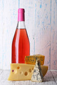 Pink wine and different kinds of cheese on wooden background — Stock Photo