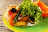 Veggie wrap filled with chicken and fresh vegetables on wooden table, close up — Stock Photo