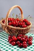 Sweet cherries in wicker basket on wooden table — Stock Photo
