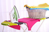 Basket with laundry and ironing board on light home interior background — Stock Photo