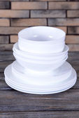 Set of white dishes on table on brick-wall background — Stock Photo